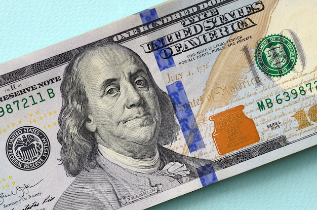 Us dollar bills of a new design with a blue stripe in the middle is lies on a light blue