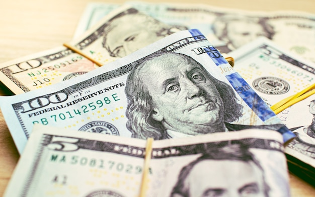 근접 촬영 사진에서 나무 테이블에 미국 달러 지폐