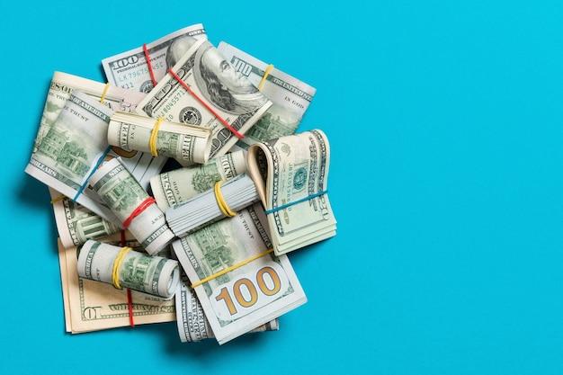 파란색 배경에 미국 달러 지폐 더미