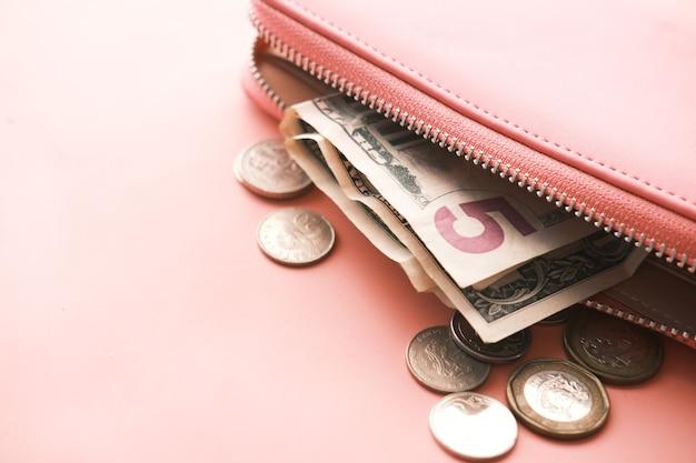 분홍색 배경에 가죽으로 된 미국 달러 현금