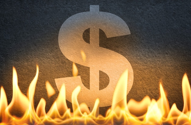 Us dollar currency symbol sign burning in fire flames, as symbol of american economy crisis, decline and usa market crash or disruption