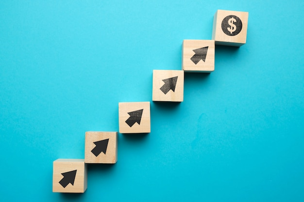 Концепция роста доллара сша и с иконами на деревянных блоках.