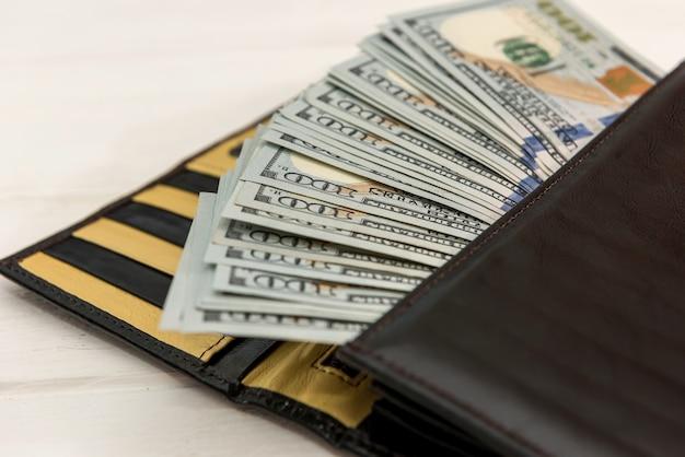 어두운 가죽 지갑에 미국 달러, 금융 개념