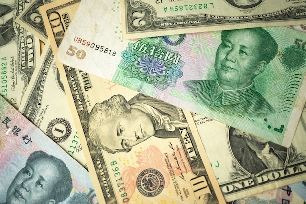 Us dollar stack and chinese yuan banknotes on the table