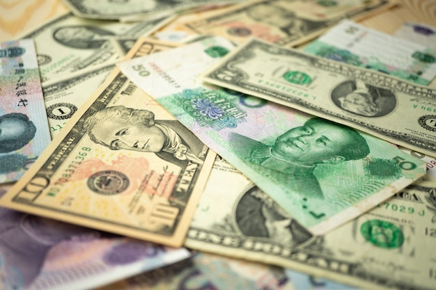 Us dollar stack and chinese yuan banknotes on the table.