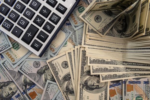 米ドル紙幣と計算機、投資または節約の概念