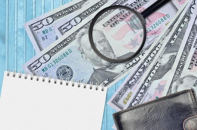 Купюры долларов сша и увеличительное стекло с черным кошельком и блокнотом