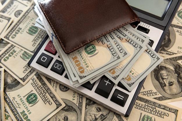 電卓付きの財布に米ドル紙幣。金融ビジネスの概念。