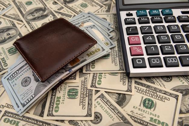 Счета долларов сша в кошельке с калькулятором. финансовая бизнес-концепция.