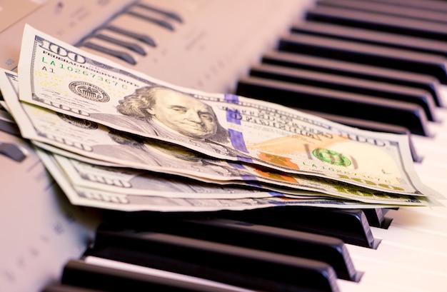 米ドルはピアノの鍵盤にあります。コンサートの支払い、音楽作品の収益