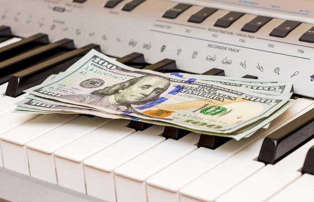 Доллары сша лежат на клавишах пианино