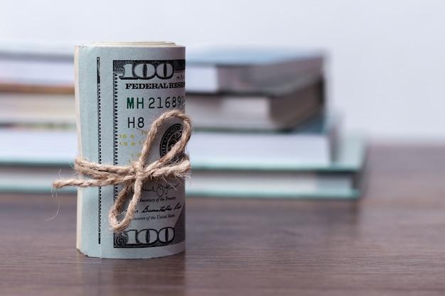 Доллары сша на фоне книг, плата за обучение, доллары свернуты в рулон возле книг