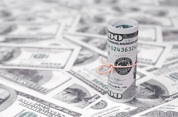Us dollars rolled up and tightened with band lies on a lot of american banknotes