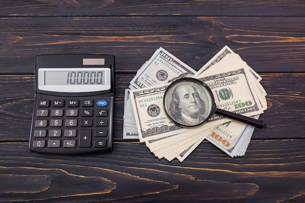 木製の背景に拡大鏡と電卓を使って米ドル。上からの眺め。