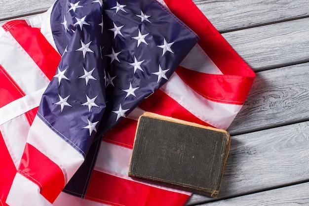 古い本の横にある米国旗。国旗に本を置く。アメリカ合衆国憲法。厳格な法律は安全を保証します。