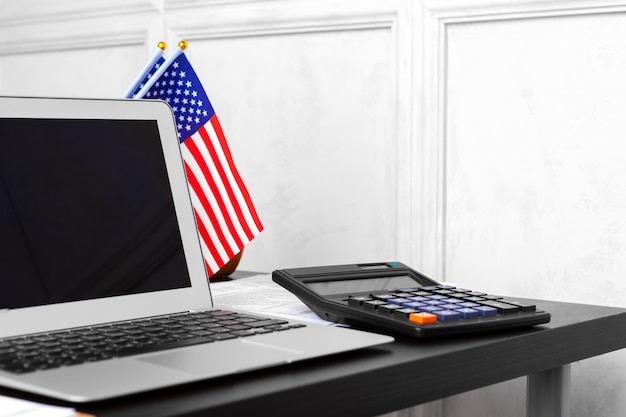 Us flag and laptop on office desk top view