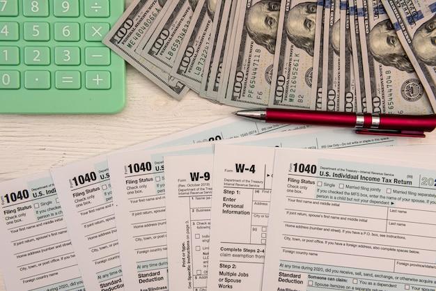 달러 지폐 계산기와 펜 서류와 함께 미국 개인 1040 양식. 회계 개념