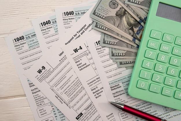 ドル紙幣計算機とペンの事務処理を備えた米国の個人1040フォーム。会計の概念