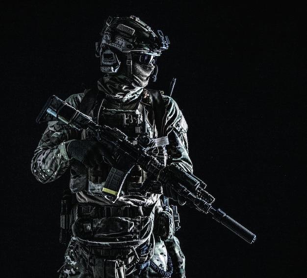 アメリカ海兵隊の射手、マスクで暗闇の中に立っている軍の特殊部隊の兵士、戦闘服、クワッドチューブ、ヘルメットの4つのレンズの暗視ゴーグル、ローキー、側面図、黒のスタジオポートレート