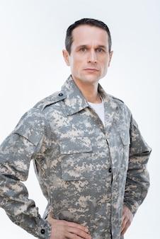 Военные сша. приятный, приятный, уверенный в себе военнослужащий смотрит перед собой и думает о своей стране, выполняя свою работу.
