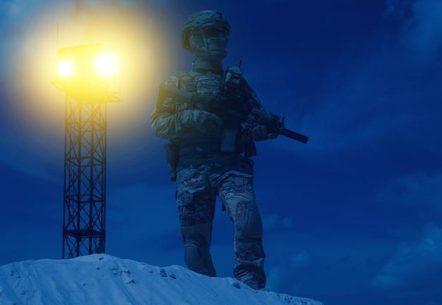 위장복, 헬멧, 마스크를 쓴 미군 보안요원은 전쟁 망루 서치 라이트의 백라이트 빔에 서 있는 돌격 소총으로 무장했습니다. 군사 기지 또는 감옥 야간 경비원