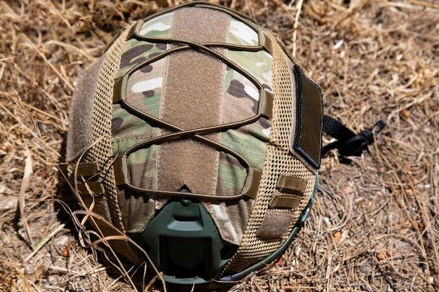 Военный тактический шлем сша на солнце. фото, изолированные на фоне сухой травы. концепция оружия для страйкбола и городских протестов. военное игровое оборудование для страйкбола в дневное время. военная форма
