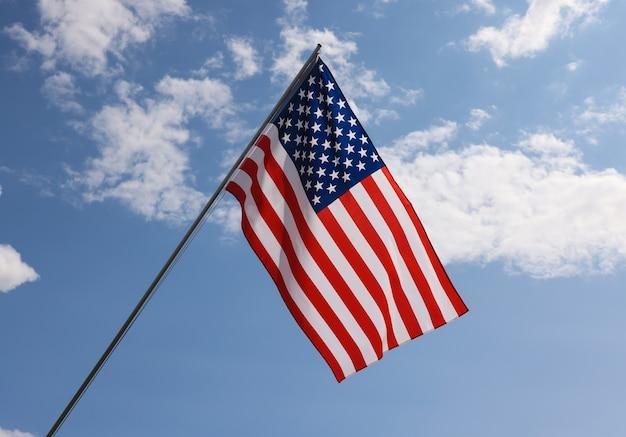 흐린 푸른 하늘 위에 깃대에 걸려 있는 미국 국기, 미국 애국심의 상징, 낮은 각도, 측면
