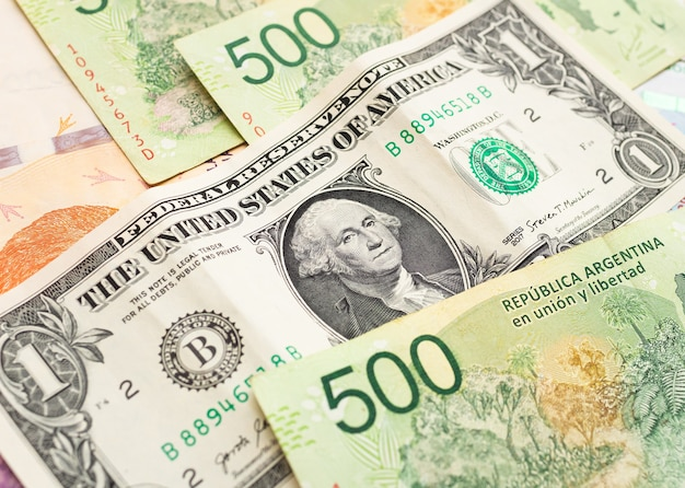 Us one dollar bill with argentine money banknotes for currency exchange concept