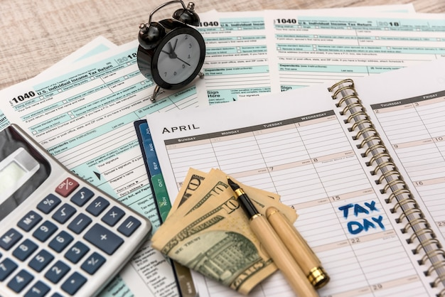 Us tax form with notepad, calculator and pen as tax concept.