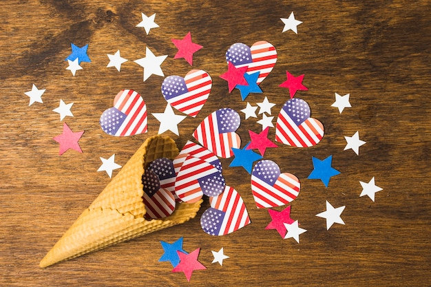Usa american flags heart shape with stars spilled from waffle cone on wooden textured backdrop