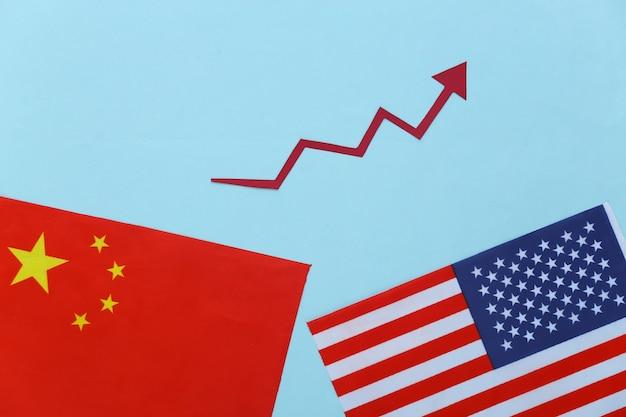 Флаг сша и китая, стрелка роста имеет тенденцию расти на синем. экономический прогресс, выход из кризиса