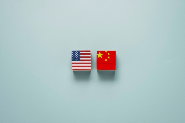 米国と中国は、青い背景の木製ブロックキューブに印刷画面を表示します。