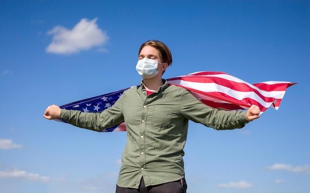 Флаг сша, молодой человек в медицинской маске держит флаг сша на фоне голубого неба