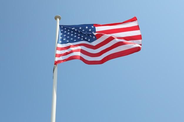 風と青い空のマットの上の米国旗アメリカ