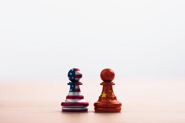 アメリカの旗と中国の旗は、明るい柔らかい背景のポーンチェスの画面を印刷します。それは、アメリカ合衆国と中国の間の関税貿易戦争税障壁のシンボルです。