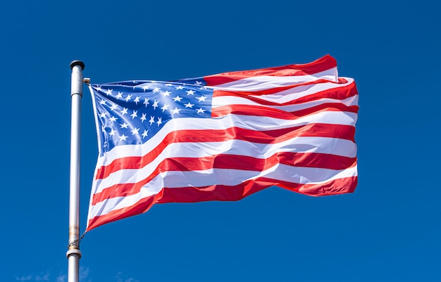 Usa flag and blue sky, american flag waving on flagpole, new york