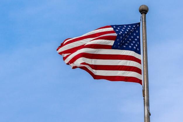 Флаг сша от флагштока, махнув на фоне голубого неба, сша, день независимости концепции