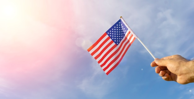 Usa flag in hand. festive usa flag in hand against blue sky and summer natural landscape. american holidays concept. high quality photo