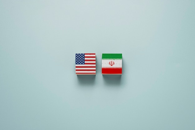 Usa flag and iran flag on wooden cube block. united state of america and iran have conflict in nuclear weapons and strait of hormuz.