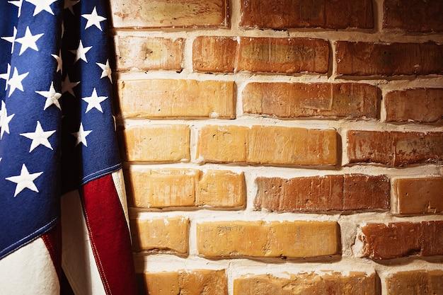 レンガの壁の近くの米国旗。テクスチャ背景画像