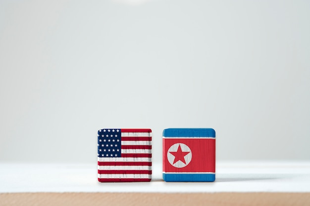 Usa flag and north korea flag print screen on wooden cubic. it is conflict for both countries in nuclear weapon military and economic sanction