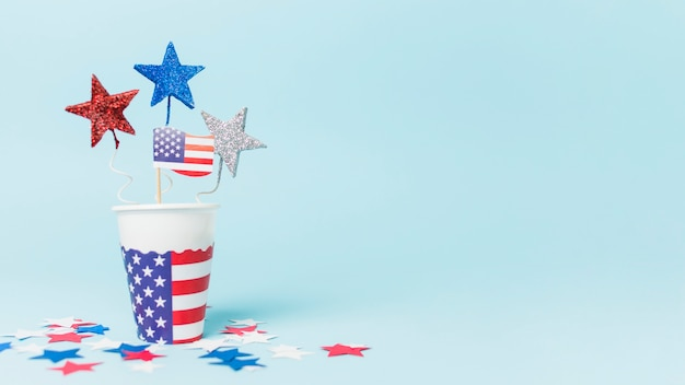 Usa flag and star props in the disposable cup against blue background