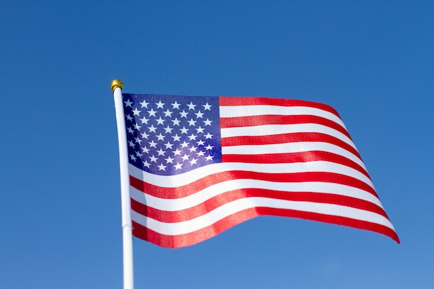 青い空に手を振っているアメリカの国旗。アメリカの国旗。アメリカの独立記念日を祝います。