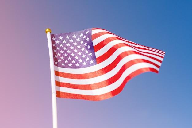 青い空に手を振っているアメリカの国旗。あなたのコンテンツのためのスペースを持つアメリカの国旗。