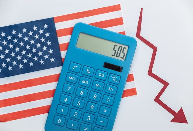 Usa flag with red fall arrow and calculator. fall graph going down. economic recession, crisis
