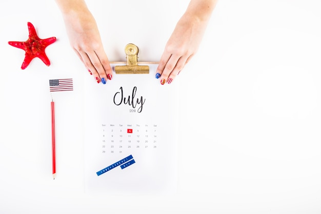 Usa independence day concept with calendar and hands above