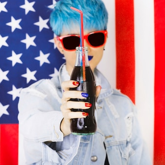 Usa independence day concept with punk woman holding bottle