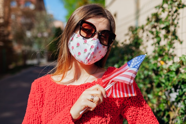 Usa independence day. woman wears protective mask outdoors holds flags during coronavirus covid-19.