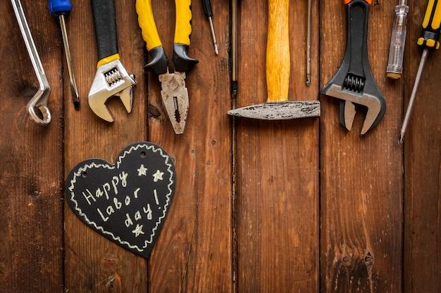 Концепция дня труда сша. различные виды гаечных ключей, подручных инструментов, бирки на деревенском коричневом фоне.