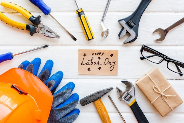 Концепция дня труда сша. различные виды гаечных ключей, подручных инструментов, бирки на белом деревенском фоне.